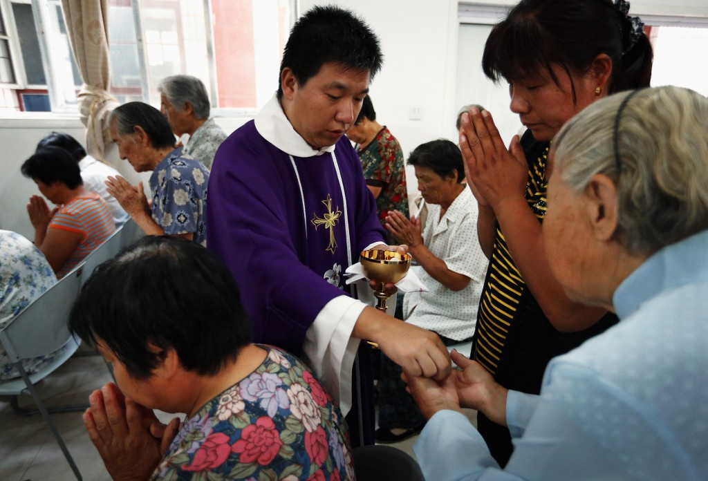 Chinese Father Liu Yong Wang distributes Communion to Catholics in a makeshift chapel in the village of Bai Gu Tun, located about 43 miles southeast of Beijing