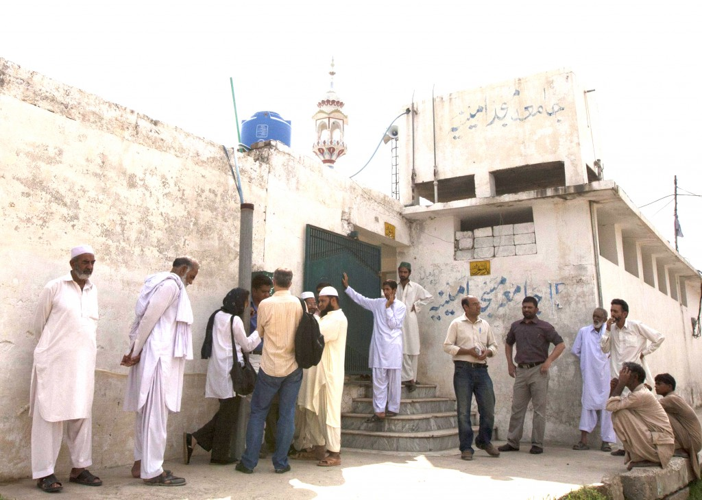 Members of the media and residents gather outside a mosque on August 23 near the locked family house of Rimsha Masih, a Pakistani Christian girl accused of blasphemy, on the outskirts of Islamabad.