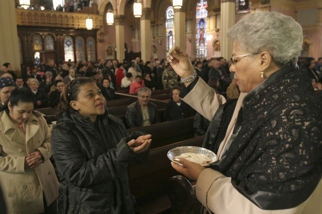 A eucharistic minister distributes Communion, all Catholics prepare to celebrate the 50th anniversary of the Second Vatican Council, all church members need to make a renewed effort to ensure laypeople are aware of their responsibility for the church.