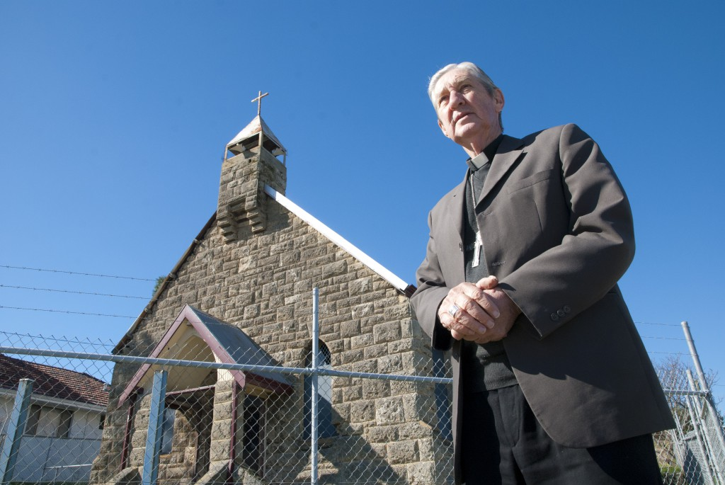 Archbishop Emeritus Barry Hickey stands outside the still-fenced-in original St Jerome's Church in Spearwood. PHOTO: Robert Hiini