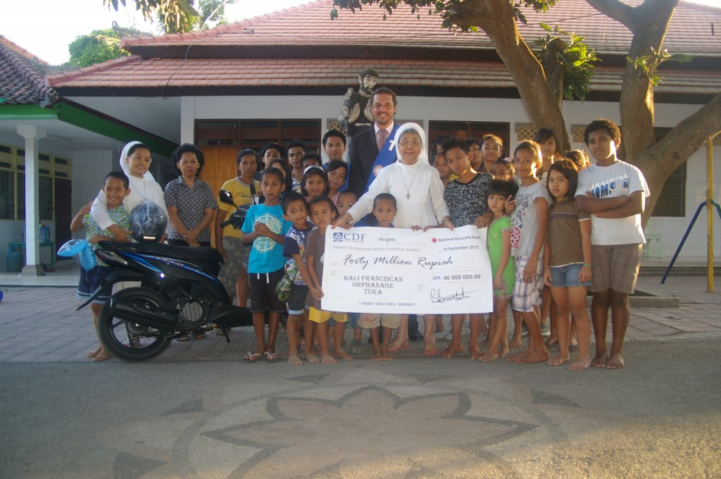 Brad Barbuto presents the orphanage with a giant cheque and a new scooter from the Knights of the Southern Cross.