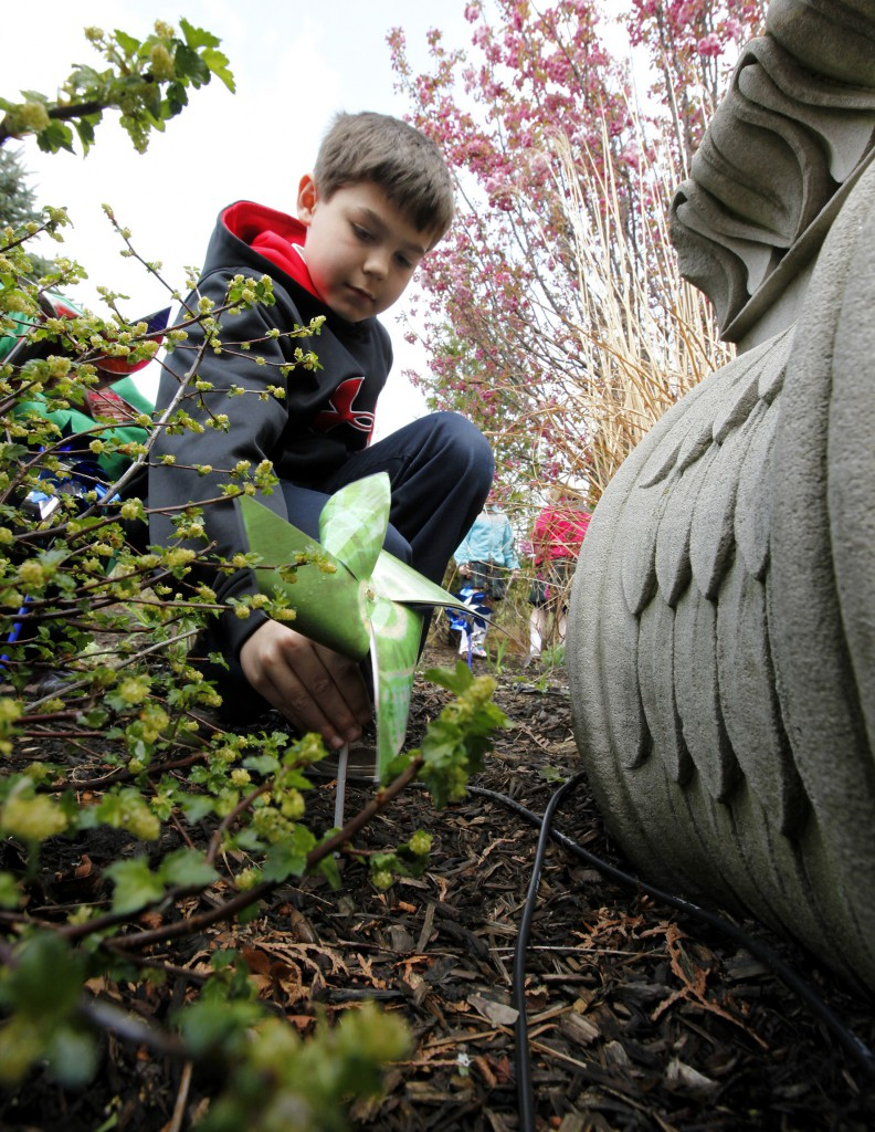 A student from St Mary of the Woods School in Chicago plants a pinwheel in the Archdiocese of Chicago's Healing Garden on March 29 during an event to launch Child Abuse Prevention Month. The Healing Garden was dedicated last year as a place of respite for the survivors of sexual abuse, their families and others affected by abuse.