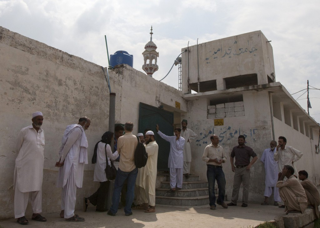 Members of the media and residents gather outside a mosque Aug. 23 near the locked family house of Rimsha Masih, a Pakistani Christian girl accused of blasphemy, on the outskirts of Islamabad in August this year..