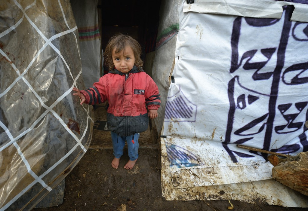 A refugee child from Syria stands outside a makeshift shelter in the village of Jeb Jennine, in Lebanon's Bekaa Valley on November 22. No one is sure how many have already arrived.