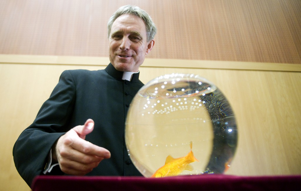 "Archbishop-designate Georg Ganswein, personal secretary of Pope Benedict XVI and prefect of the papal household, stands next to a fish bowl on December 11 during the presentation of the Italian-language children's book ""The Mystery of a Little Pond"" in Rome."