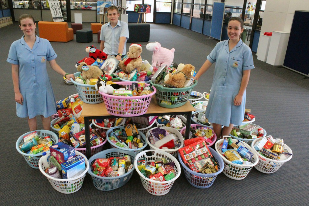 Rockingham students, christine, conner and skye, with the hampers they assembled.