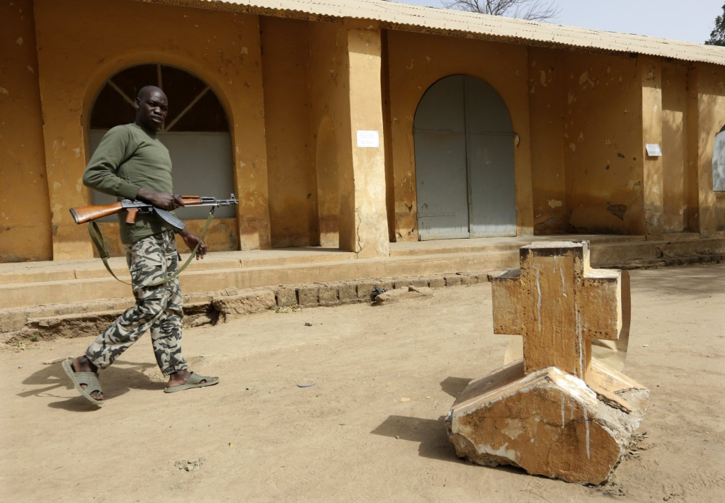 A Malian soldier walks past a cross from the church seen in the background in the recently liberated town of Diabaly on January 24. PHOTO: Erik Gaillard, Reuters