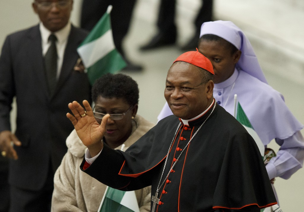 Cardinal John Olorunfemi Onaiyekan of Abuja, Nigeria, waves as he greets guests before Pope Benedict XVI's audience on Nov. 26 2012 in Paul VI hall at the Vatican. PHOTO: CNS/Paul Haring