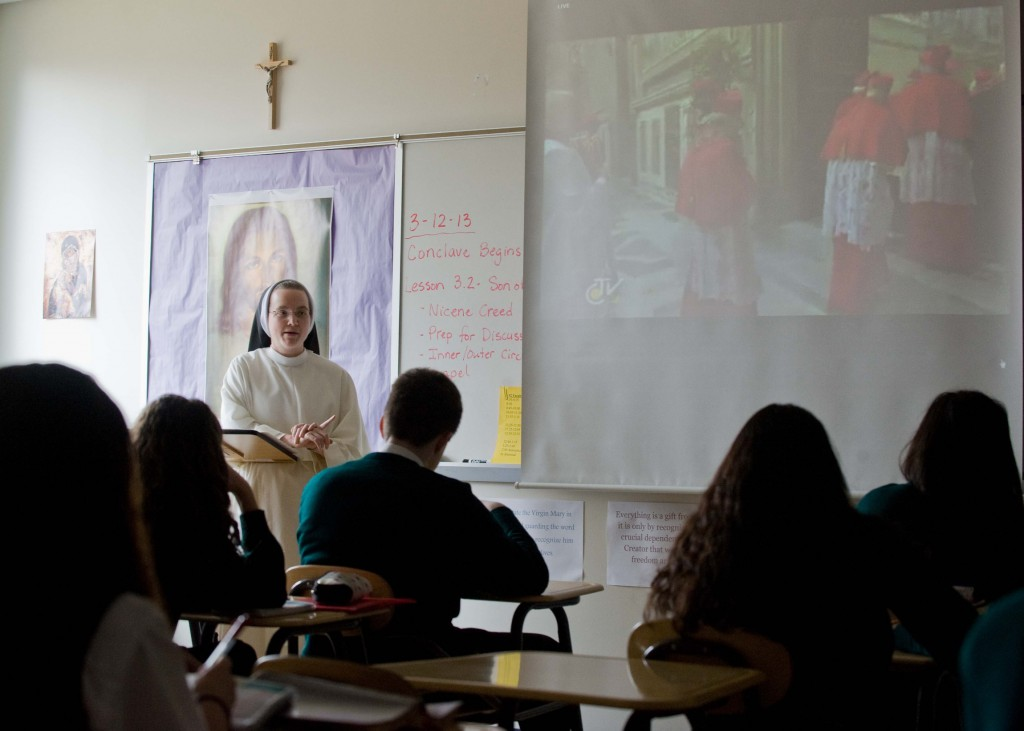Dominican Sister Mary Grace Watson speaks with students on March 12 in her religion class at John Paul the Great High School in Dumfries, Va., as they watch a live TV feed from the Vatican during the papal conclave in Rome. PHOTO: CNS/Matthew Barrick