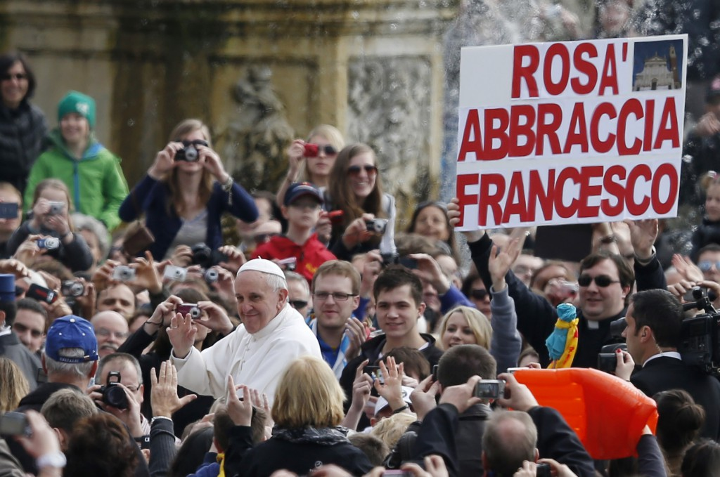 "A priest holds a sign in Italian saying ""Rosa embraces Francesco"" as Pope Francis arrives to lead his general audience in St. Peter's Square at the Vatican April 3. Rosa is a city in Italy. PHOTO: CNS/Paul Haring"