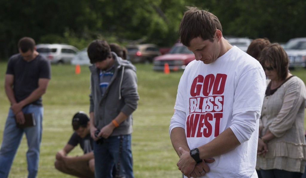 Town residents bow their heads in prayer during an April 21 outdoor prayer service four days after a deadly fertilizer plant explosion in the town of West, near Waco, Texas. PHOTO: CNS/Adrees Latif, Reuters