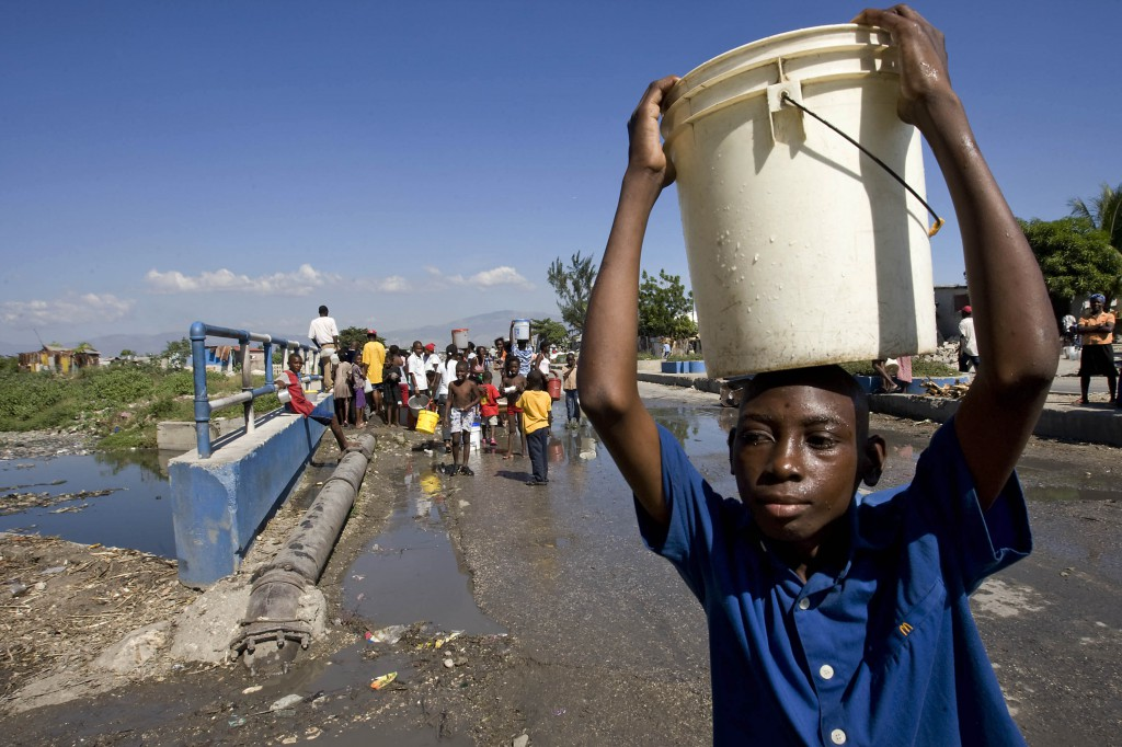 A boy carries a hard-won bucket of water away from a broken water pipe in the Cite Soleil neighborhood of Port au Prince, Haiti, Jan. 15, in this handout photo from the United Nations. PHOTO: CNS/Logan Abassi, United Nations