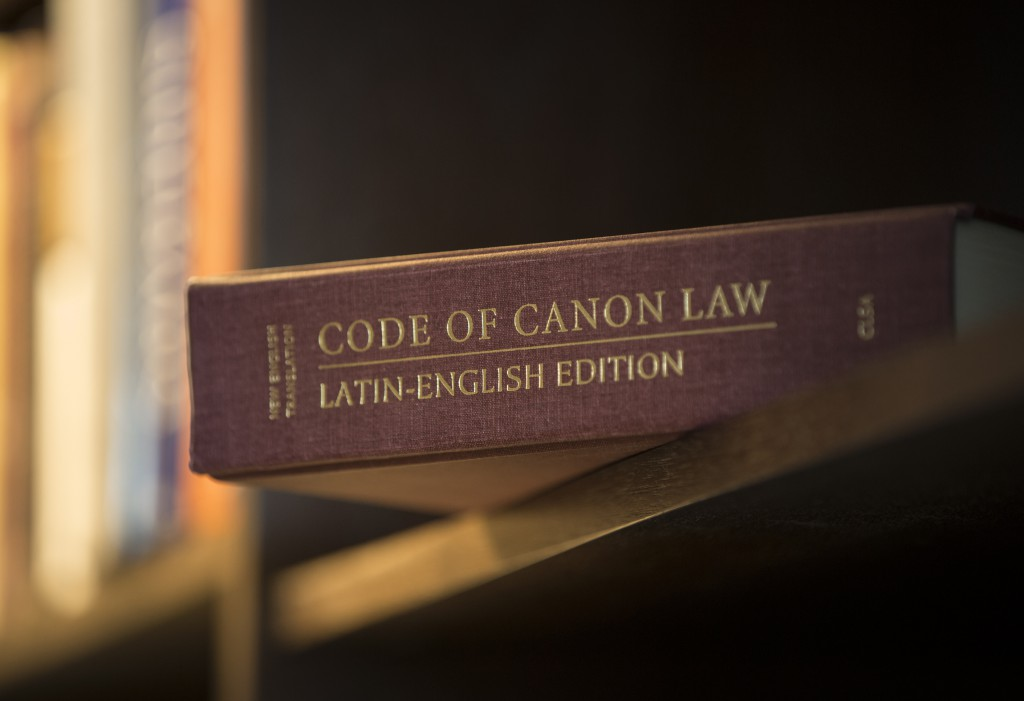 "A Latin-English edition of the Code of Canon Law is pictured on a bookshelf. The Pontifical Council for Legislative Texts is drafting text for a new ""Book VI: Sanctions in the Church"" section of the code dealing with offenses and penalties. PHOTO: CNS"