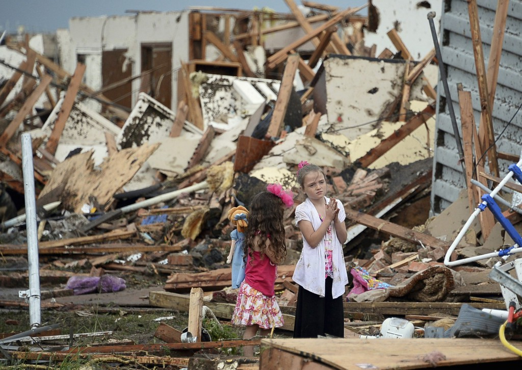 Two girls stand in rubble after a tornado struck Moore, Okla., May 20. The mile-wide tornado touched down near Oklahoma City, killing dozens, including many children, destroying homes, businesses and a pair of elementary schools in the suburb of  Moore. PHOTO: CNS/Gene Blevins, Reuters