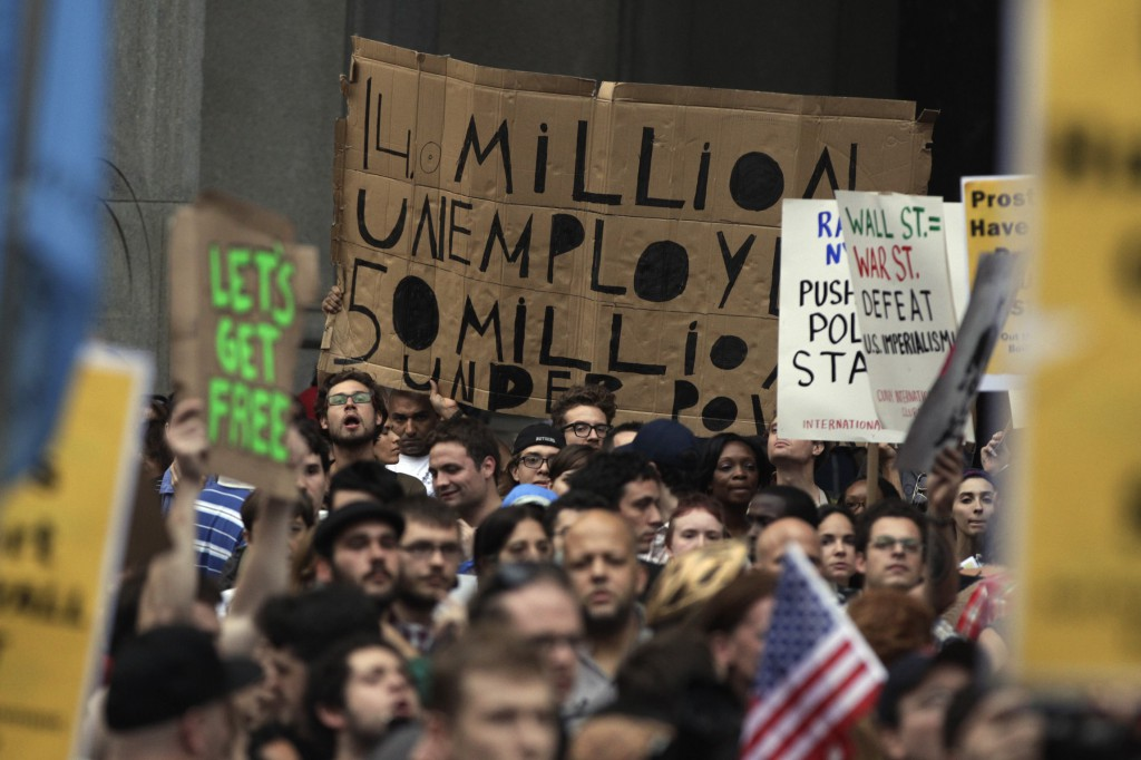 Demonstrators from the Occupy Wall Street campaign hold signs in 2011 as a protest march enters the courtyard near the New York Police Department headquarters. PHOTO: CNS/Lucas Jackson, Reuters