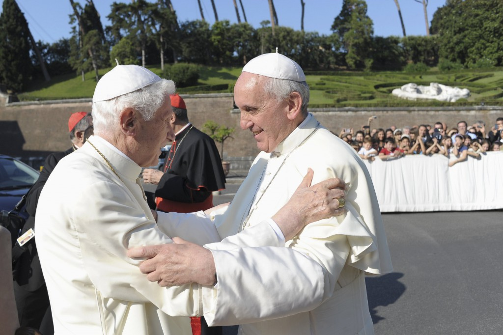 Pope Francis, right, embraces retired Pope Benedict XVI during a ceremony in the Vatican gardens July 5. During the service,  Pope Francis blessed a new statue of St. Michael the Archangel and recited separate prayers to consecrate Vatican City to St. Joseph and to St. Michael. PHOTO: CNS/L'Osservatore Romano via Reuters