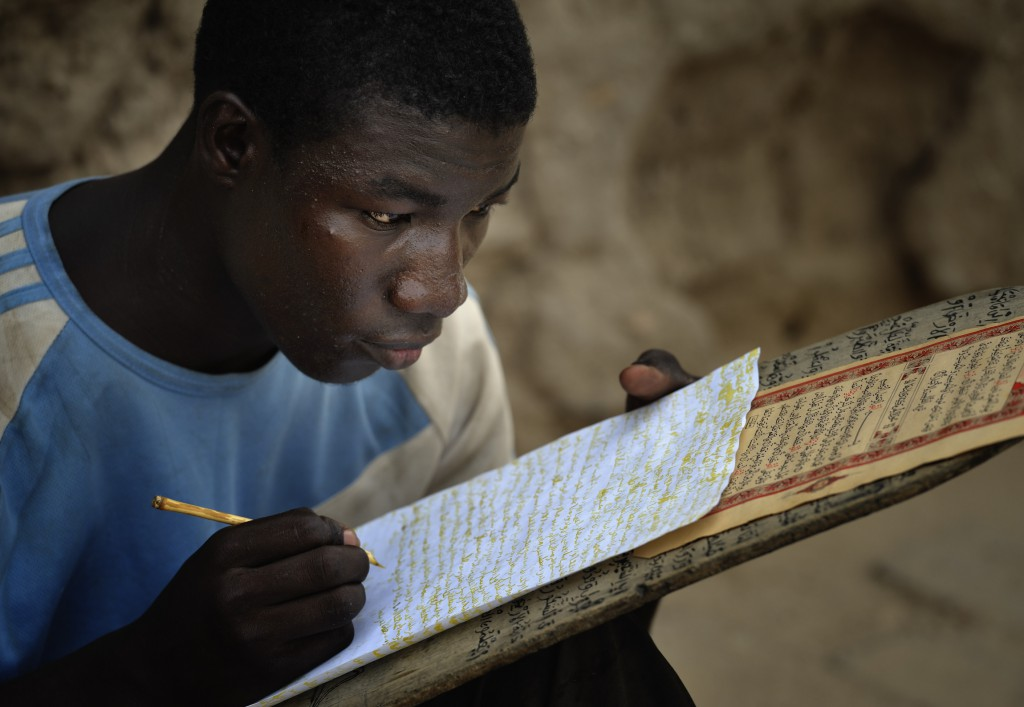 A boy copies Quranic verses in a Muslim school in June in Timbuktu, the northern Mali city that was seized by Islamist fighters in 2012 and then liberated by French and Malian soldiers in early 2013. The people of the ancient city suffered and many fled under the rebel takeover. Now, many have yet to return home as the crisis in the north shows no signs of waning. PHOTO: CNS/Paul Jeffrey