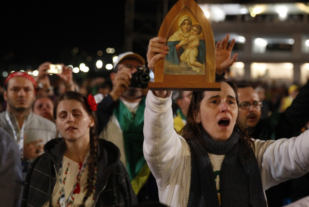 A woman holds an icon during the Eucharistic adoration led by Pope Francis on July 27 at the World Youth Day vigil on Copacabana beach in Rio de Janeiro. PHOTO: CNS/Paul Haring