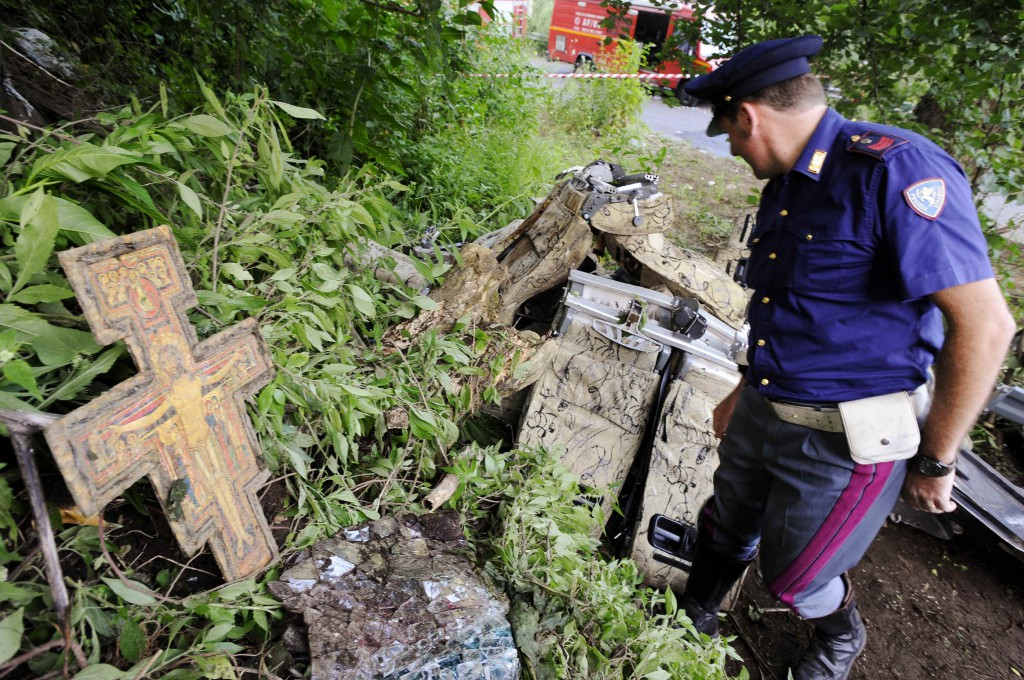 A crucifix is seen as a policeman surveys the wreckage of a bus that crashed near the town of Avellino in southern Italy July 29. At least 38 people died when the bus filled with pilgrims returning from a Catholic shrine tour plunged off an elevated highway. PHOTO: CNS/Ciro De Luca, Reuters