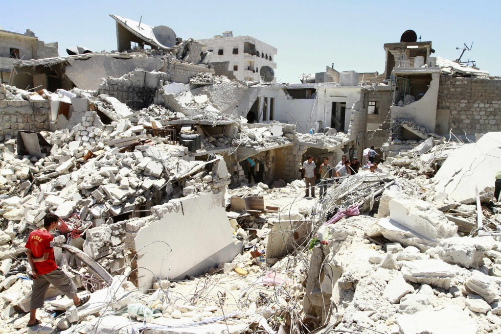 Residents rummage through the damage and debris left of their homes for their belongings after what activists said was an air attack on July 27 from forces loyal to Syria's President Bashar Assad in Aleppo. PHOTO: CNS/Hamid Khatib, REuters
