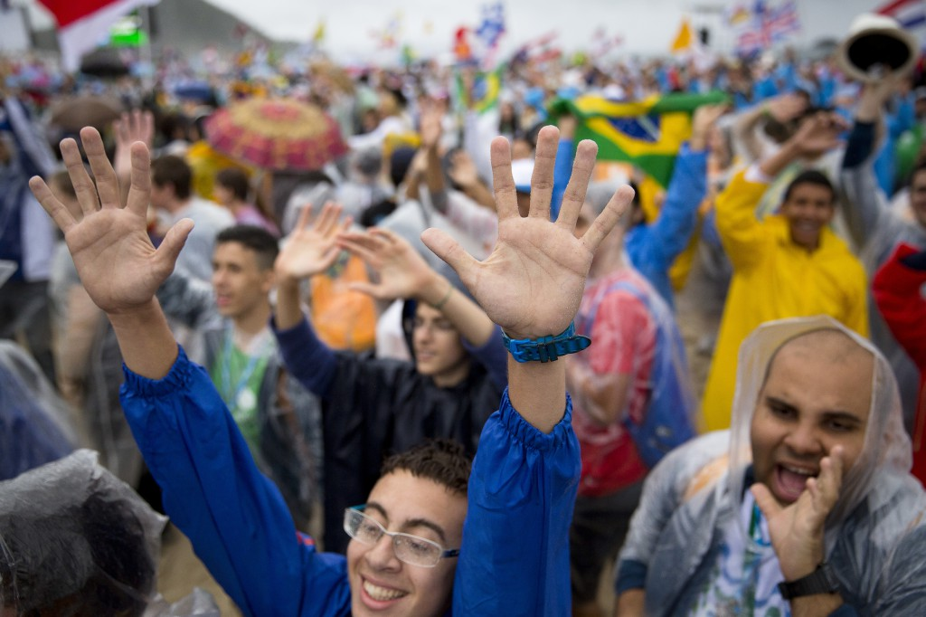 Pilgrims wave to television cameras during the opening Mass of World Youth Day in Rio de Janeiro July 23. Young Latin Americans say they are more excited to take their faith to the street after the weeklong celebration. PHOTO: CNS/Tyler Orsburn