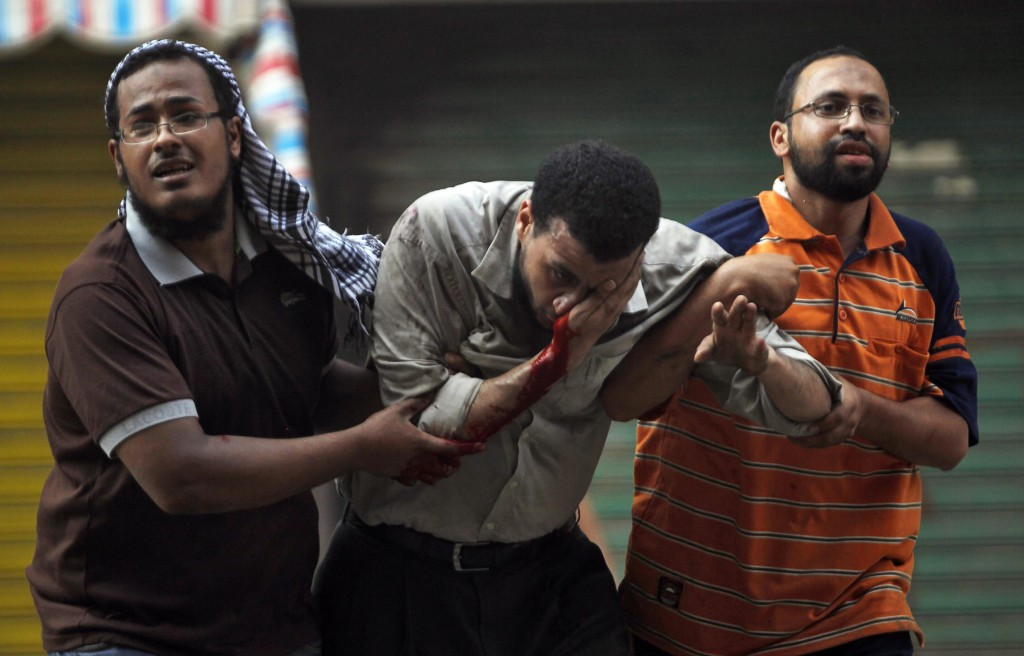 Protesters who support ousted Egyptian President Mohammed Morsi assist an injured demonstrator during clashes outside a police station in Cairo Aug. 16. A prominent Egyptian bishop said his country will not have a civil war, and international bodies should not intervene. PHOTO: CNS/Amr Abdallah Dalsh, Reuters