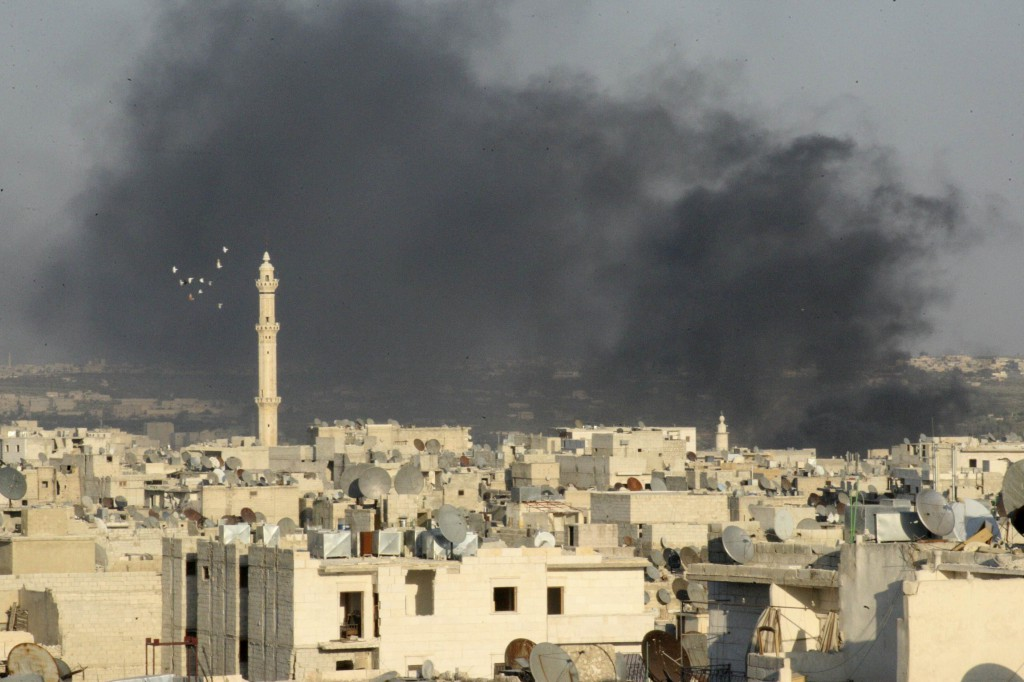Smoke rises amid buildings in Aleppo, Syria, Sept. 4.  Christian leaders of the Holy Land gathered there Sept. 7, as Christians and Muslims all over the world prayed with Pope Francis for Syria. PHOTO: CNS/Ammar Abdulla, Reuters