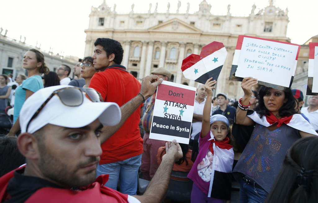 People from Syria hold up signs before a prayer vigil led by Pope Francis in St. Peter's Square at the Vatican Sept. 7. The pope called for the worldwide day of fasting and prayer for peace in Syria, the Middle East and the world. PHOTO: CNS/Tony Gentile, Reuters