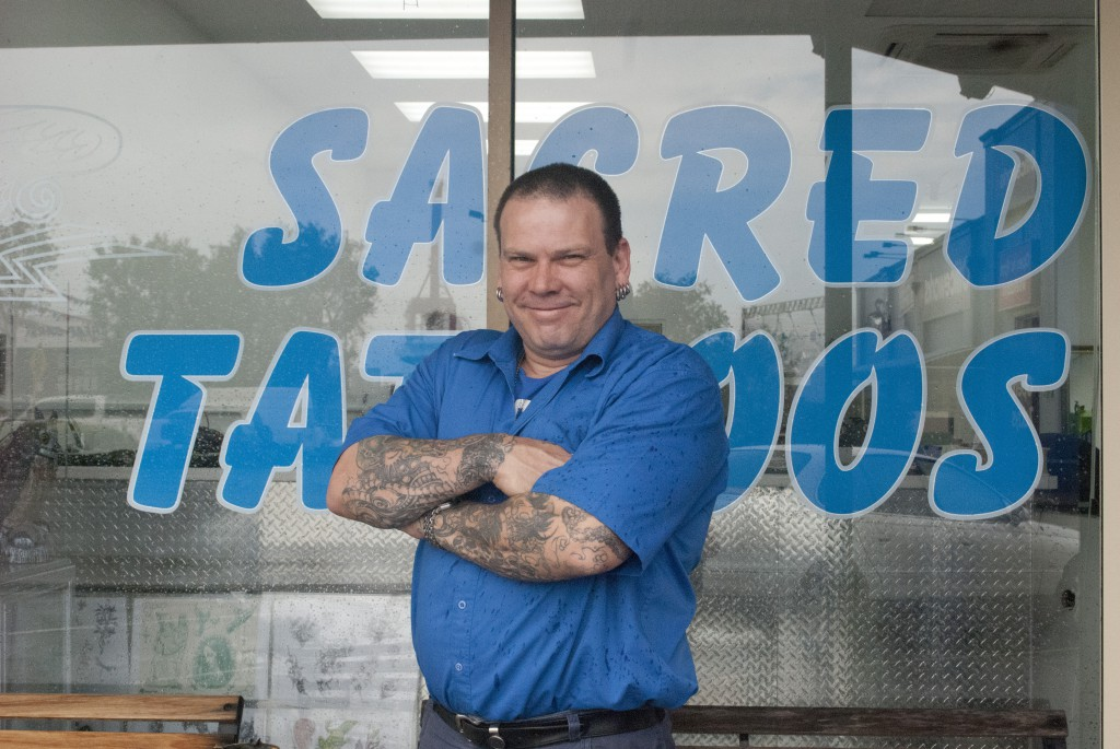 Stuart Randell outside his Fremantle tattoo parlour, at left. Some of the designs he offers to clients, below at left. Inside the parlour, customers and inquirers are greeted by the sight of an ancient Bible near the reception workstation. The computer screen carries a sticker reading 'Jesus loves me with or without my tattoos'. PHOTO: Matthew Biddle
