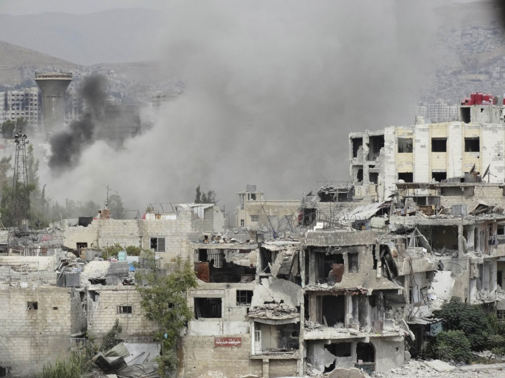 Smoke rises from behind a building in Damascus, Syria, Sept. 18. Two bombings a day later killed at least 39 people in the latest surge in violence. PHOTO: CNS/Msallam Abd Albaset, Reuters