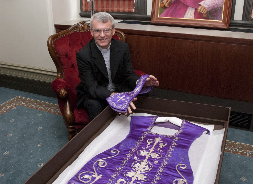 Archbishop Timothy Costelloe SDB examines the historic vestments in his Perth office. Made at the Royal Workshop in Spain in the 1830s, the vestments are thought to have been used by Archbishop Costelloe's predecessor, Bishop Jose Maria Serra OSB. PHOTO: Robert Hiini