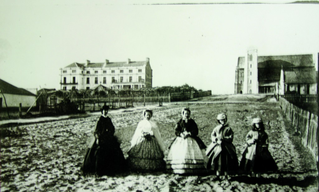 A photograph taken by AH Stone in 1868 shows five prominent Perth ladies out for a stroll. They are the Governess, Maria Stone, left; Maria's sister, Miss Helms and friends of the family. The photograph is taken in Victoria Avenue, Perth. In the background are the Bishop's palace, completed in 1856 on the left, and the Cathedral of the Immaculate Conception of the Blessed VIrgin Mary, completed in 1865. Directly in front of the cathedral is the smaller St John's Church, the first Catholic church in WA. PHOTO: Courtesy of Mrs Dorothy Croft