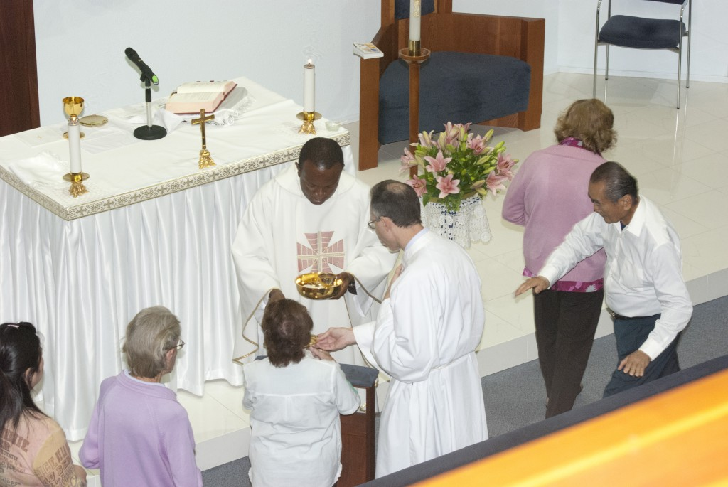 Visiting priest Fr Emmanual Dimobi distributes Holy Communion at All Saints' Chapel, where two kneelers are in place for communicants. PHOTO: M BIDDLE