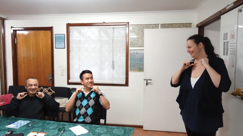 "Auslan teacher Emma Chevron shows seminarians Gerard Nemorin and Joseph Hoang the sign for ""priest""."