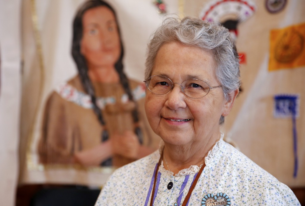 Sister Kateri Mitchell, a Mohawk and a Sister of St. Ann, is the executive director of the Tekakwitha Conference, poses July 26 in front of a banner depicting St. Kateri at the 75th annual Tekakwitha Conference in Fargo, N.D. PHOTO: CNS/Nancy Wiechec