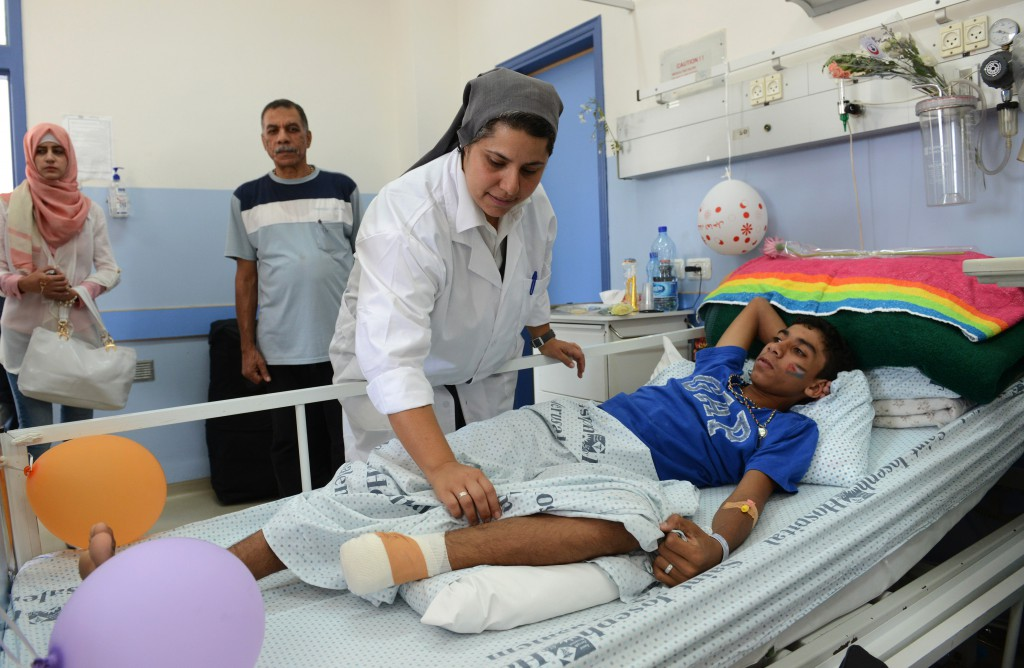 Sister Muna Totah, a member of the Sisters of St. Joseph of the Apparition, works on Karim Nofal, 15, of  Gaza, at St. Joseph Hospital in Jerusalem July 30. The teenager is one of 23 Gaza patients being treated at the hospital, which specializes in head- and chest-trauma wounds. PHOTO: CNS/Debbie Hill