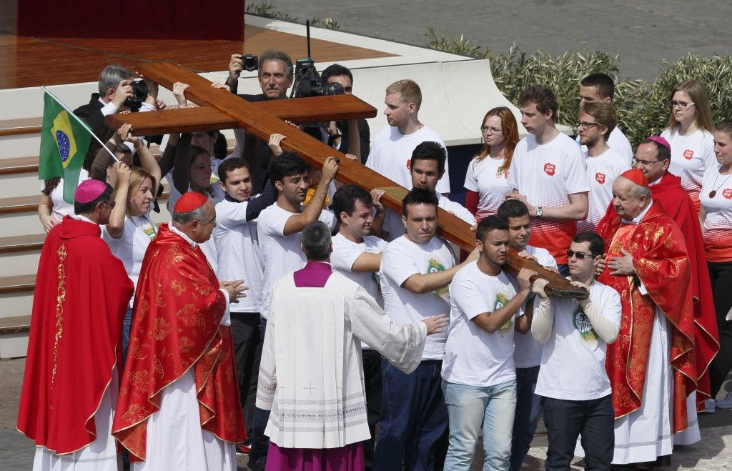 Young people from Brazil, left, pass on the World Youth Day cross to youths from Poland, right, at the conclusion of Pope Francis' celebration of Palm Sunday Mass in St. Peter's Square at the Vatican April 13. The next  international Catholic youth gathering will be July 25-Aug. 1, 2016, in Krakow, Poland. Watching at left is Brazilian Cardinal Orani Joao Tempesta of Rio de Janeiro and at right Polish Cardinal Stanislaw Dziwisz. PHOTO: CNS/Paul Haring