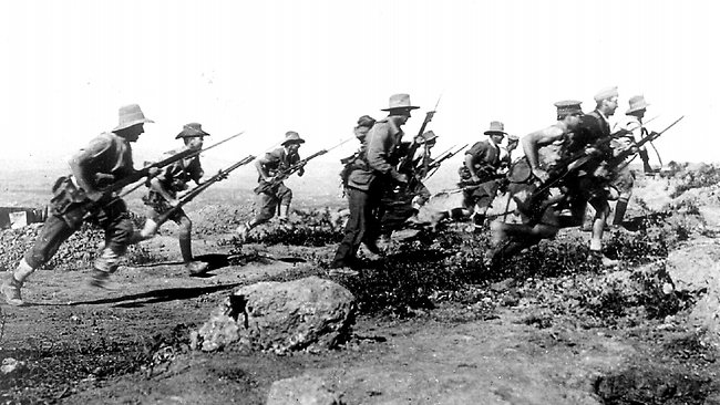 Australian soldiers at Anzac Cove in 1915 enact a charge for the official photographer. PHOTO: Australian War Memorial/Supplied
