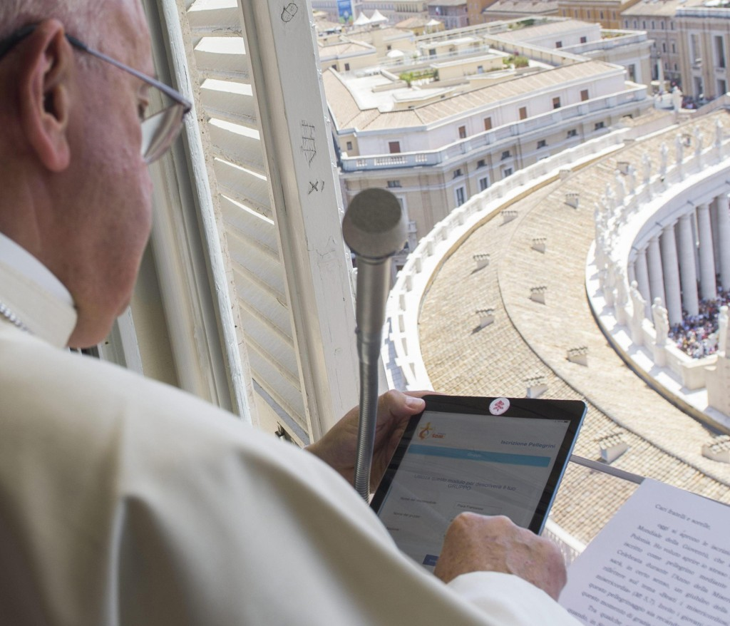 Pope Francis uses a tablet to officially open online registration for World Youth Day 2016 in Poland during the Angelus at St. Peter's Square July 26. PHOTO: CNS