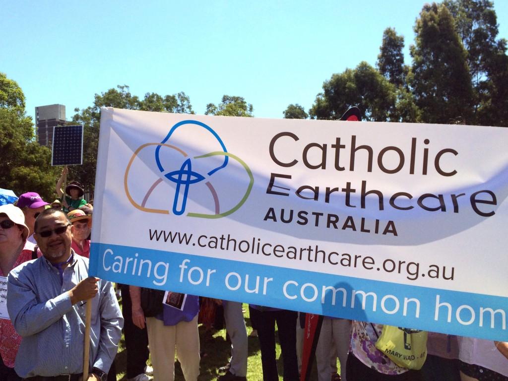 Francis Leong from Catholic Mission holds the Catholic Earthcare Australia banner. Photo courtesy Carol Mitchell