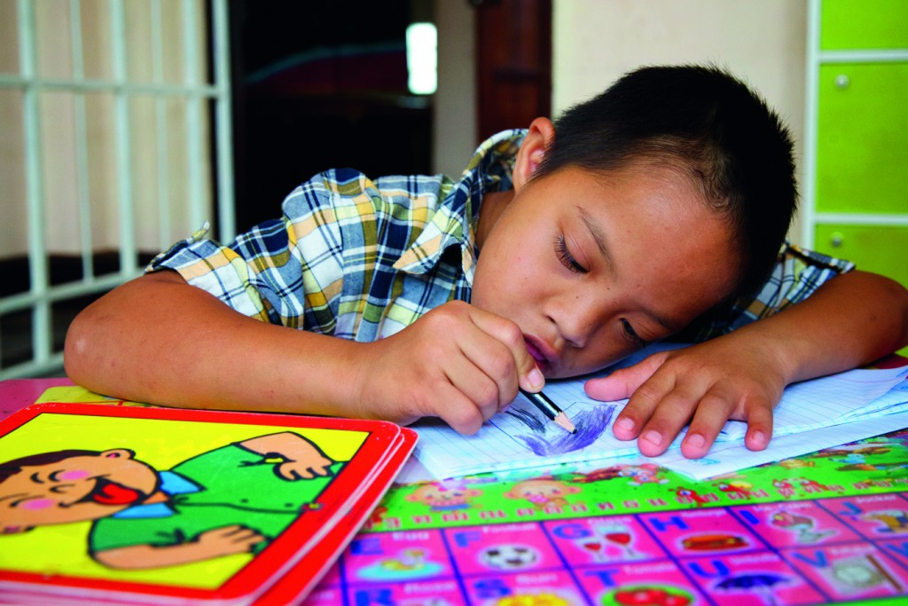 """Hum Noy concentrating hard during a lesson. """"Hum Noy is learning how to follow instructions and say the names of his teachers and friends,"""" says his mother, Duangmala. Photo: Richard Wainwright"""