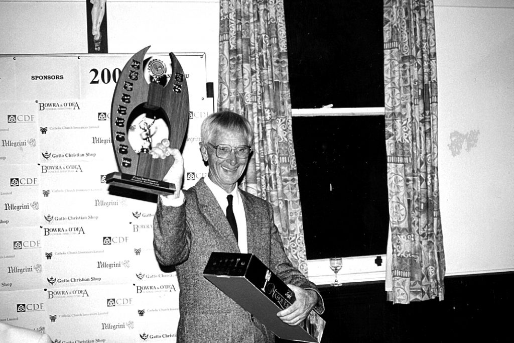 A proud and fair sportsman, Fr Peter St John holds up a trophy he won for playing his favourite sport: tennis. Photo: Supplied