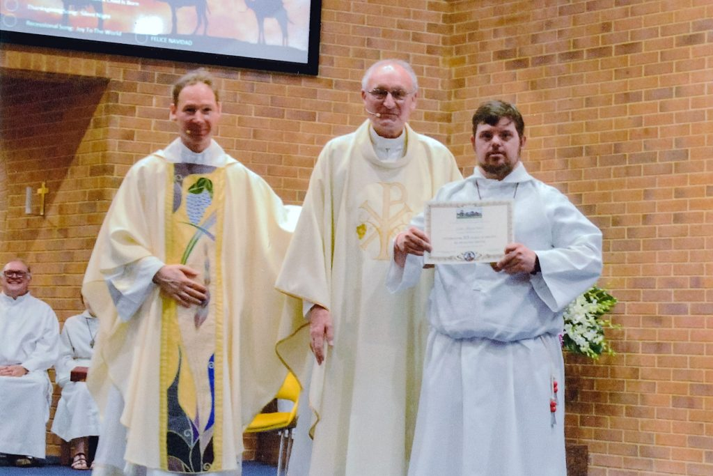 Fr Thomas Zureich with Thornlie Parish Priest Mgr Tim Corcoran presenting senior altar server Luke McLachlan with his certificate commemorating his 25 years of service as an altar server. Photo: Supplied