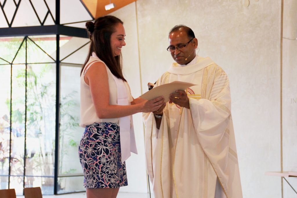 Eleisha Hathaway receiving her certificate from College Chaplain Fr Alfred Saminedi after being fully initiated in the Catholic Church Photo: Supplied
