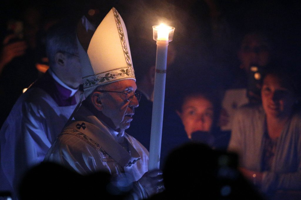 Pope Francis carries a candle as he arrives to celebrate the Easter Vigil in St Peter's Basilica at the Vatican on 15 April 15. Photo: Paul Haring/CNS