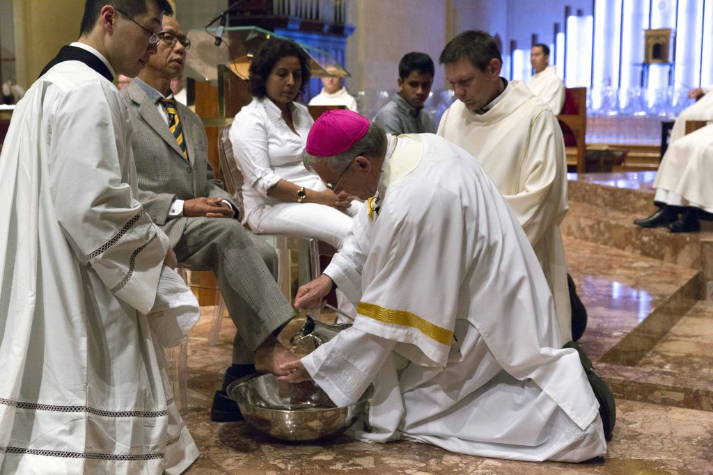 The Archbishop washing the feet of others at the Mass of the Lord's Supper on Holy Thursday, following in the example of Jesus, representing the call to serve with humility and selflessly. Photo: Ron Tan