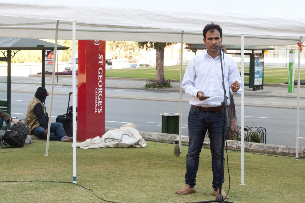 Iranian refugee and poet, Arad Nik speaking at the Palm Sunday Walk for Refugees, held at St George's (Anglican) Cathedral. Photo: Caroline Smith