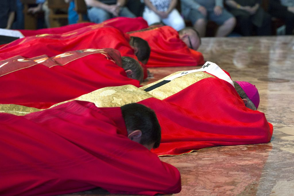 Archbishop Costelloe and concelebrants lie prostrate on the sanctuary on Good Friday, in an act of complete worship of the crucified Christ who gave his life for our salvation. Photo: Ron Tan