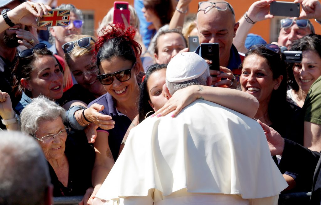 A woman kisses Pope Francis as he arrives for a visit at the parish of San Pier Damiani on 21 May at Casal Bernocchi on the outskirts of Rome. Photo: CNS/Remo Casilli, Reuters.