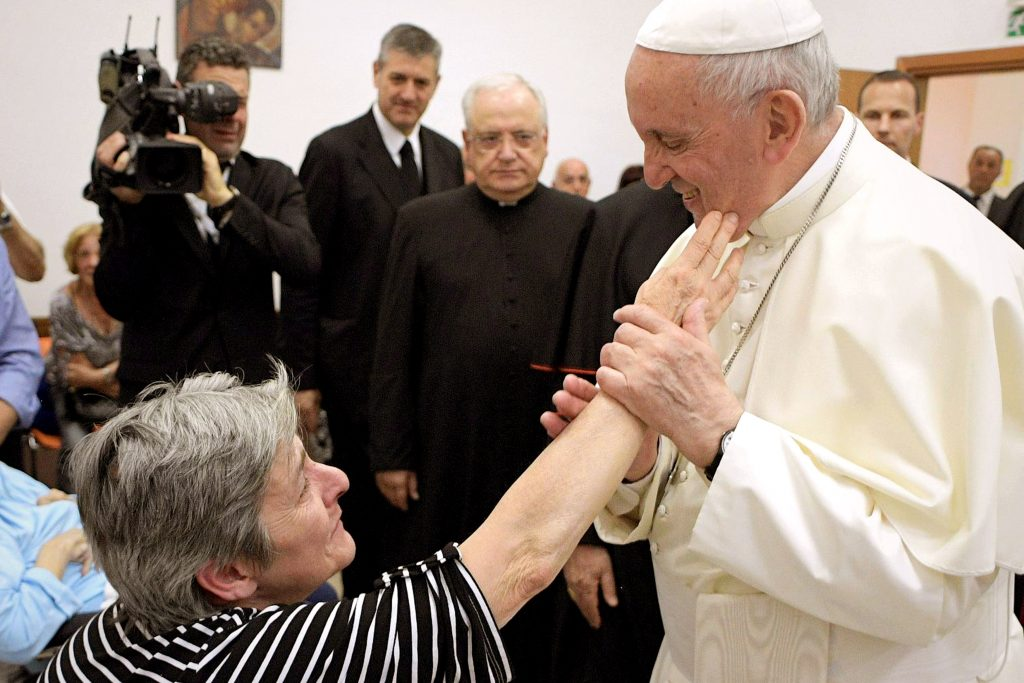 A woman touches Pope Francis' cheek during a visit to the parish of San Pier Damiani on 21 May at Casal Bernocchi on the outskirts of Rome. Photo: CNS/Remo Casilli, Reuters.